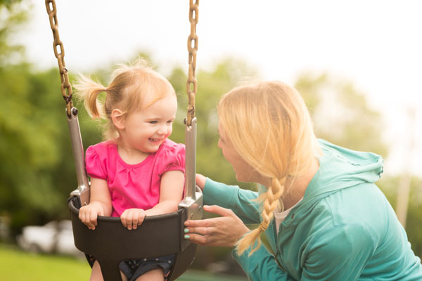 Babysitter with little girl on swing