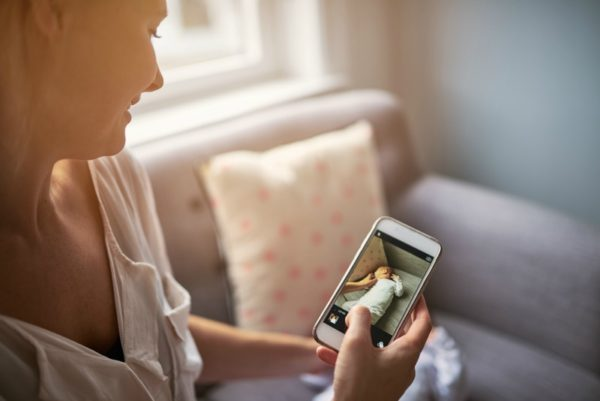 woman sitting on lounge looking at pictures on her phone