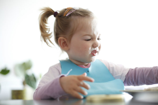 toddler girl picking at food making a funny face