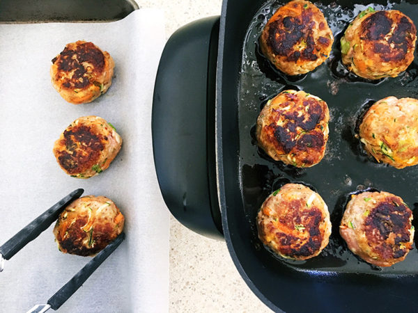 turkey and vegetable rissoles frying in a pan