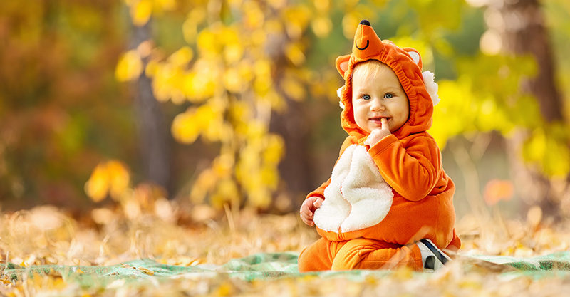 Baby dressed as a fox sitting in garden
