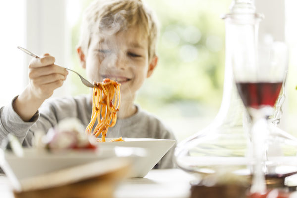 Boy eating spaghetti at table.