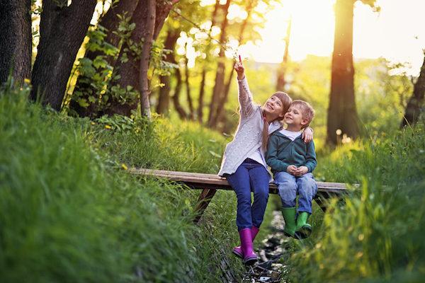 Children sitting on log in forest