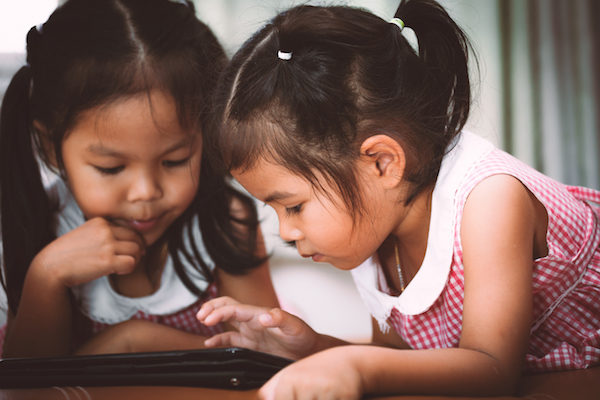 Two girls playing with tablet