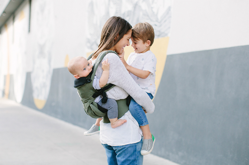 mother holding preschooler and baby in ergobaby omni carrier