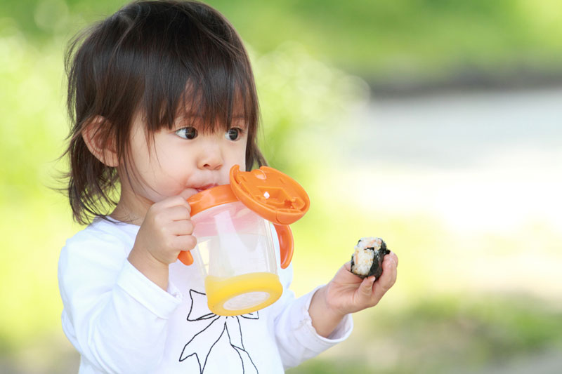 Toddler girl holding sippy cup