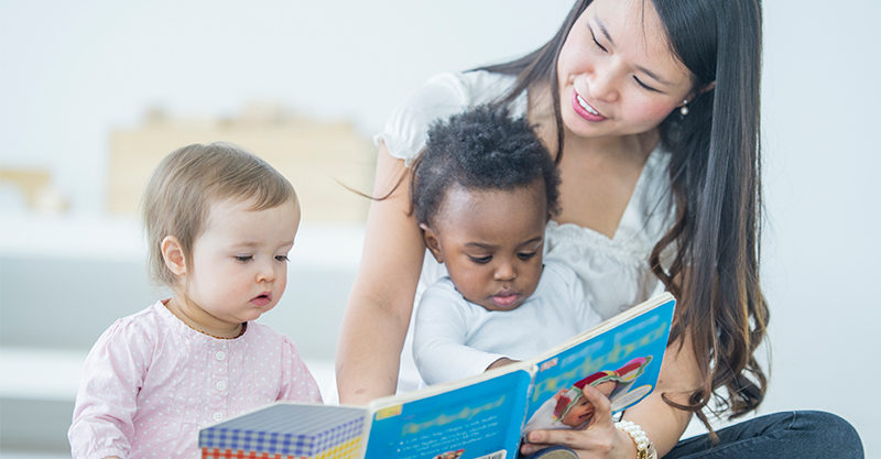 Two toddlers being read to by young woman