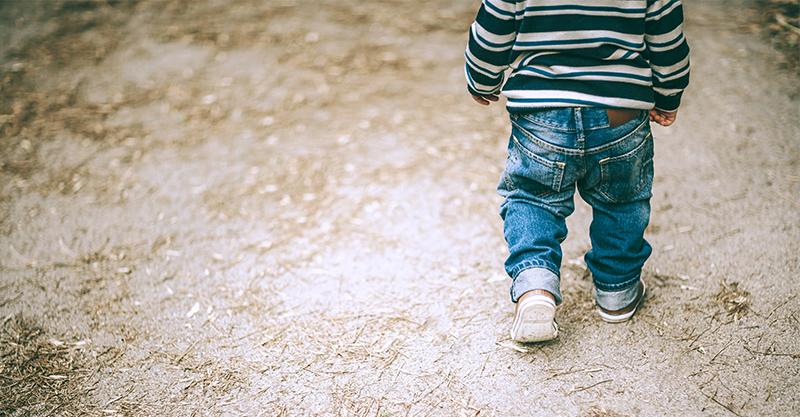 Little boy walking on road