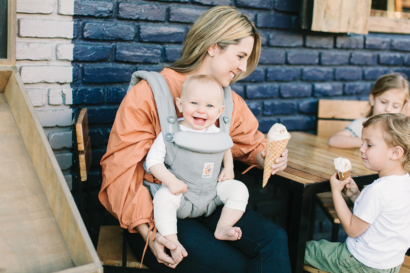 mother and children at cafe with ergobaby omni carrier