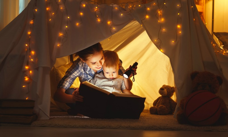 reading story in tent mother child