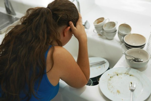 woman with dirty dishes at sink