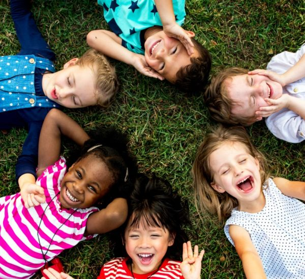 Kids lying on the grass smiling