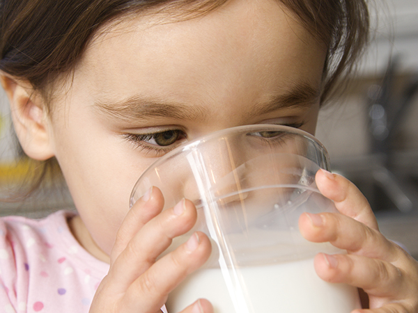 Toddler drinking a glass of milk