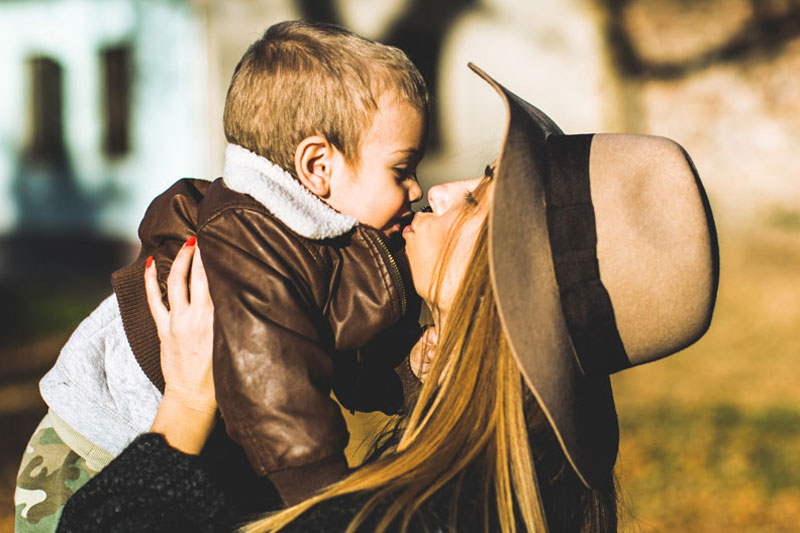 Mother kissing son wearing hat