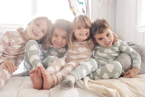 four kids in pyjamas sitting on a bed