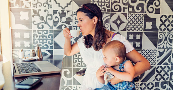 Working mum drinking coffee with toddler