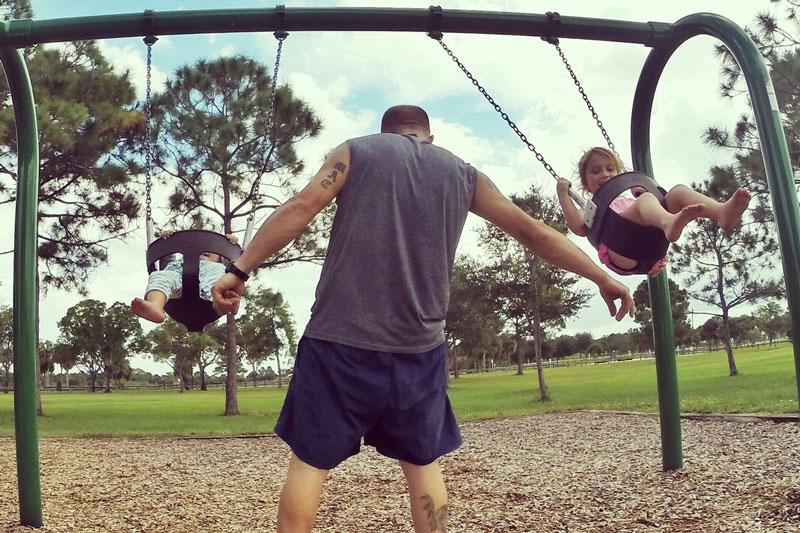 Dad pushing kids on swing