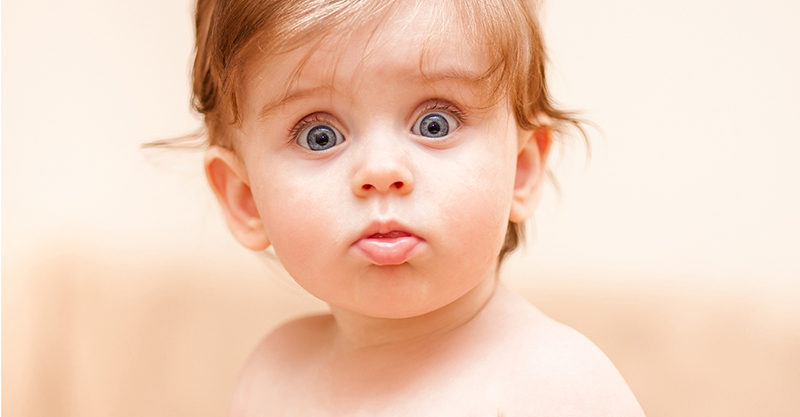 naked little kid staring at the camera.