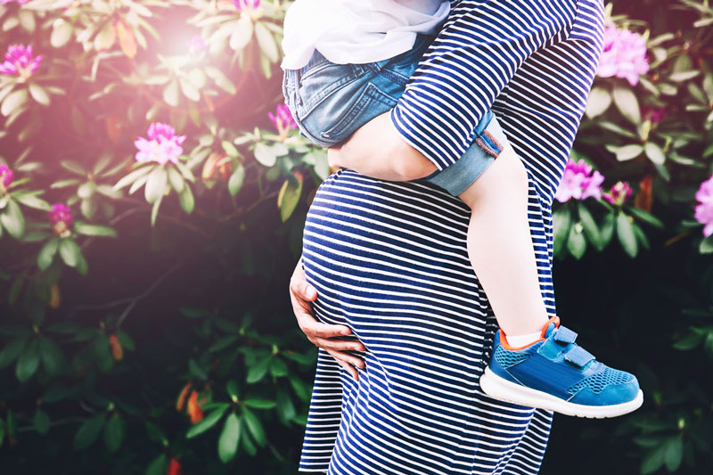 Pregnant mum carrying toddler