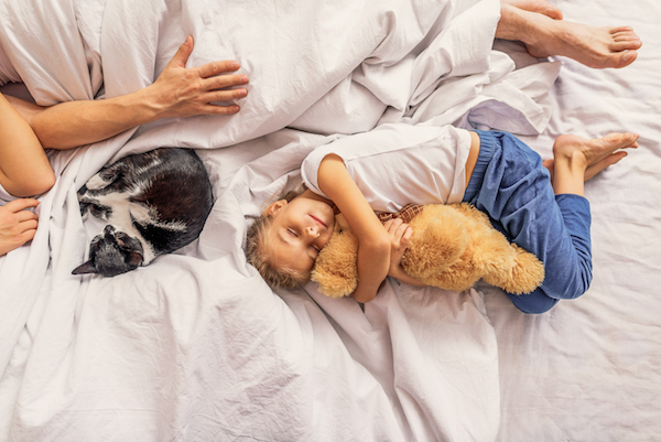 Family relaxing together on bedroom