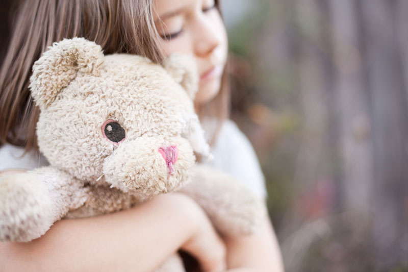 Toddler cuddling stuffed bear