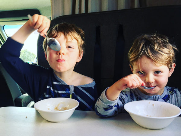 Two boys eating breakfast in a campervan