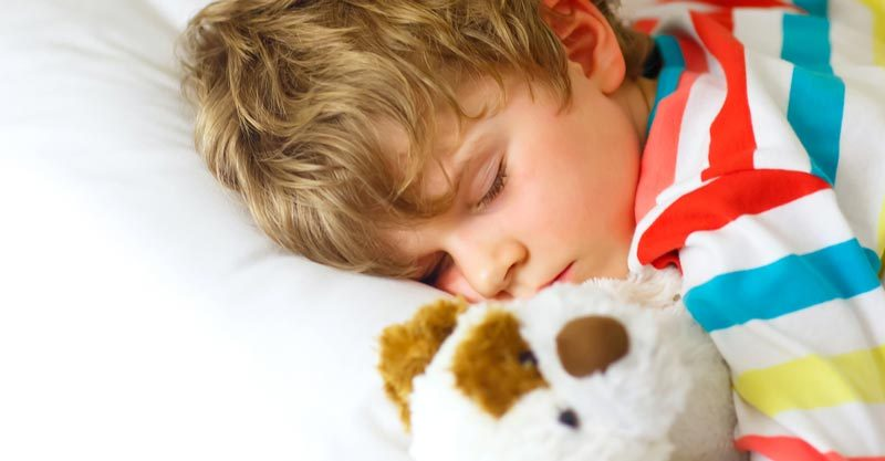 Little boy asleep with teddy