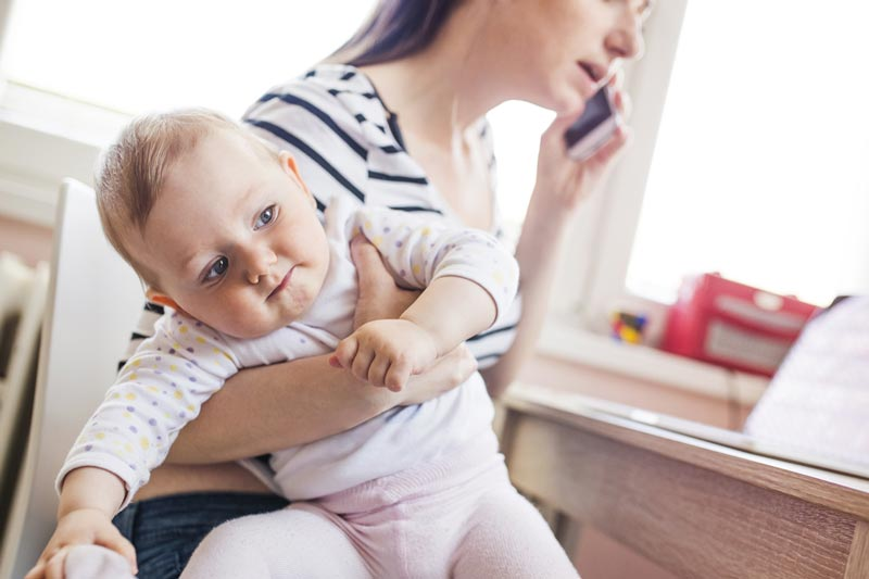 Mum on phone with baby in arms