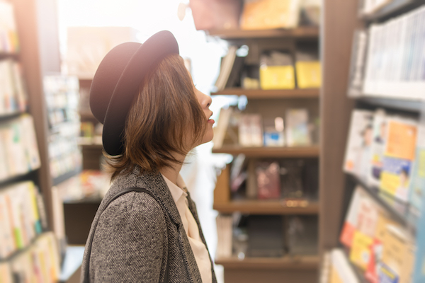 Young woman looking for books in store
