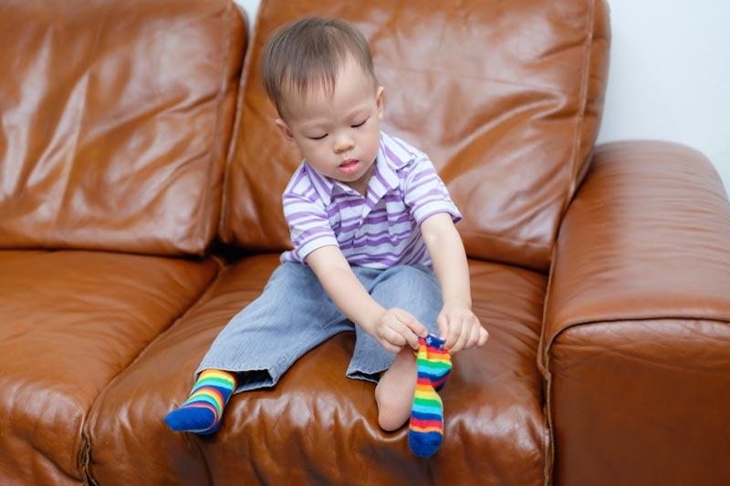 Toddler boy putting on socks