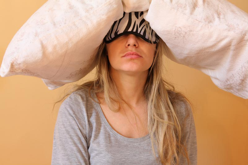 Tired mum with pillow on head