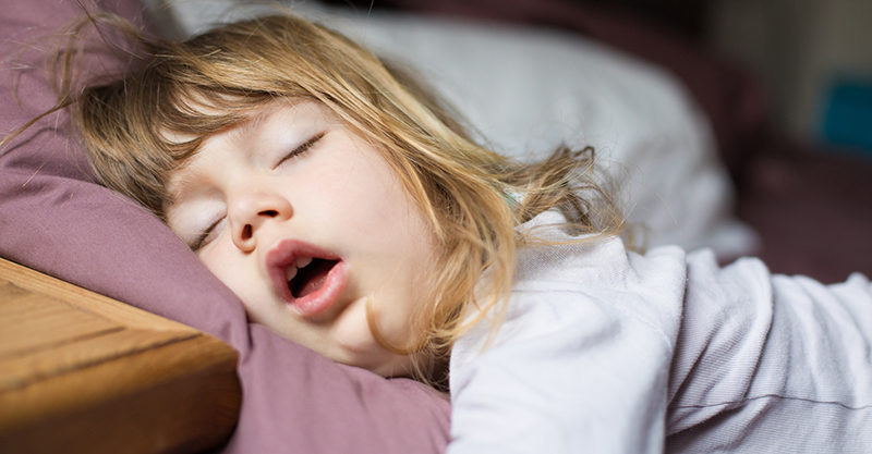 Toddler girl asleep in bed with mouth open