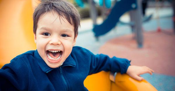 Toddler boy on slippery dip at playground