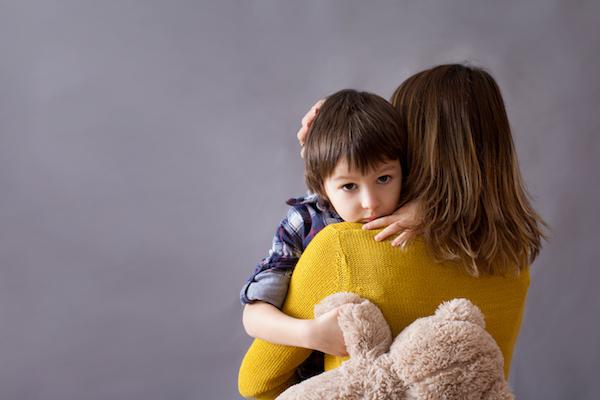 Little boy sad hugging mum