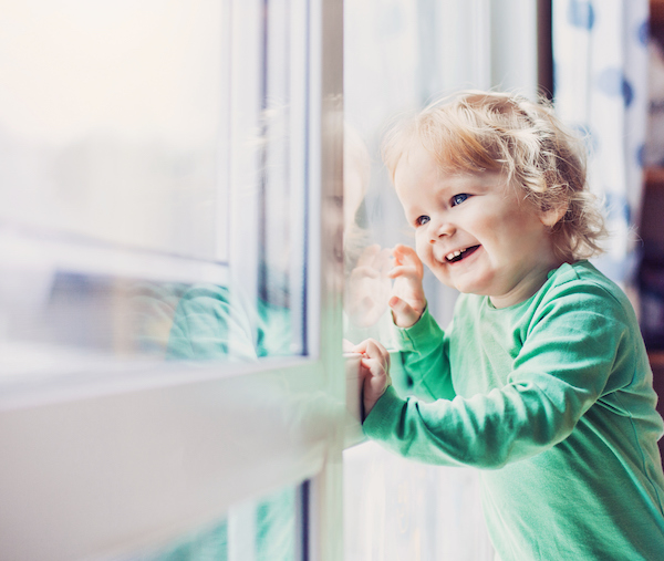 Smiling happy baby looking out window