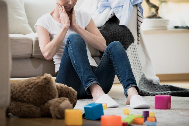 Frustrated mum sitting on floor with toys