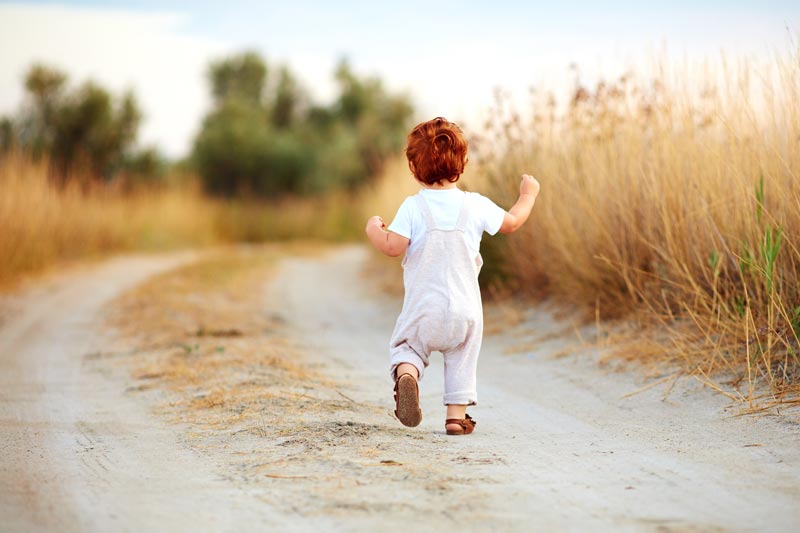 Toddler running in field red hair