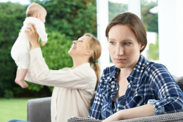 Sad woman jealous of friend with baby