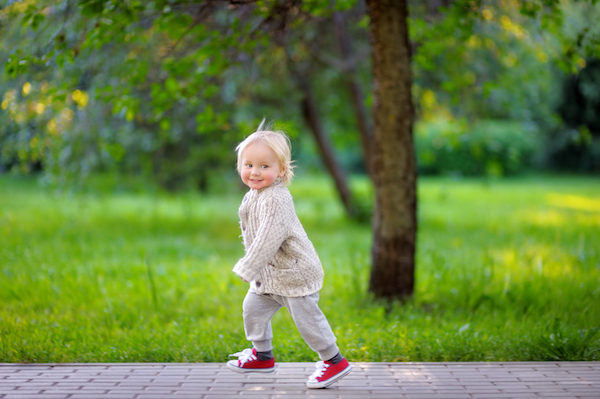 EDITORIAL: Toddler boy running outside in park