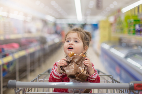 Toddler girl eating pretzel in supermarket