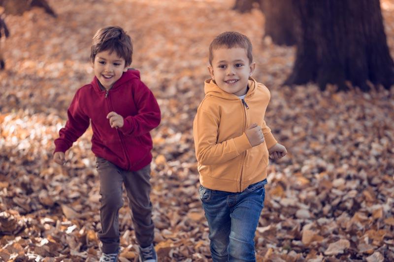 Boys running in autumn leaves