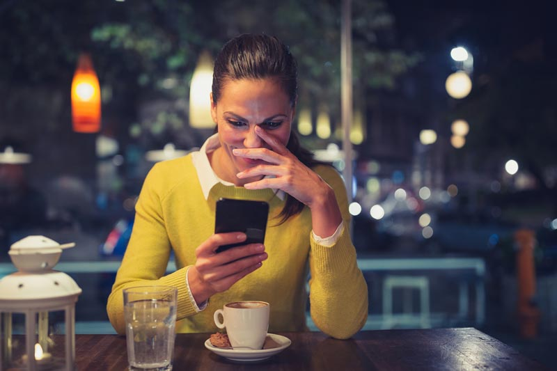Woman looking at phone in cafe