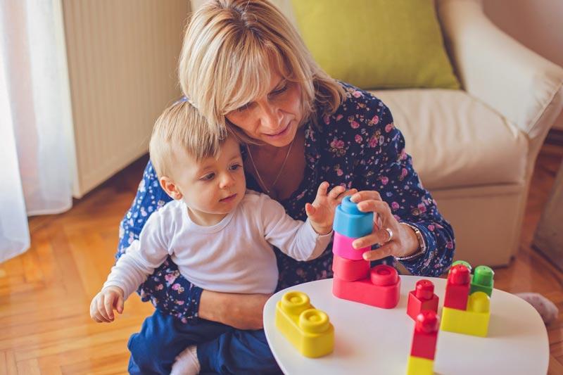 Toddler playing blocks with grandma