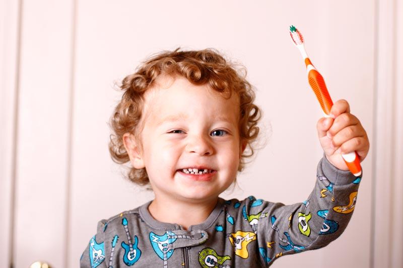 Boy wearing pyjamas holding toothbrush