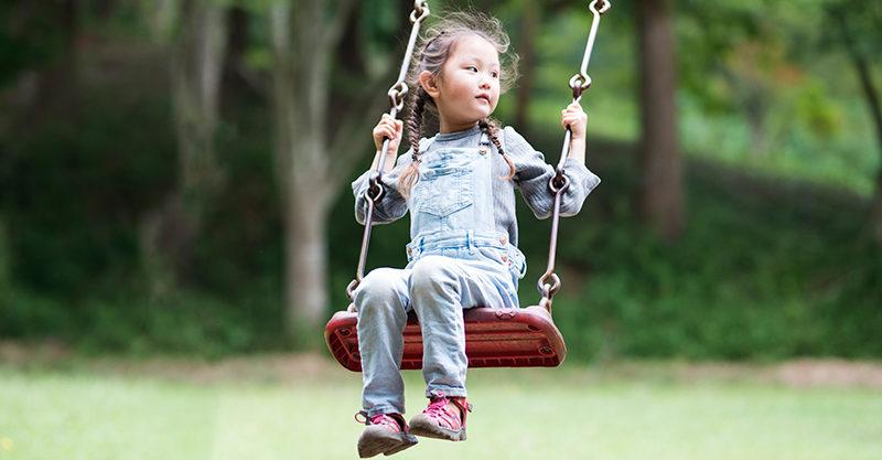 Girl on a swing outside in park