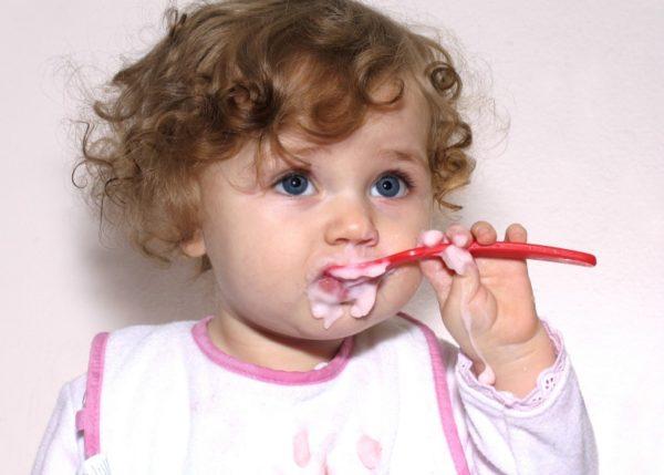 left handed girl holding spoon