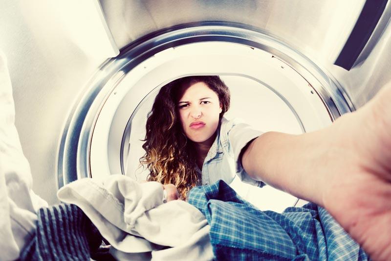 Annoyed woman looking in washing machine