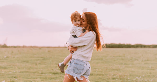 Young mum with toddler hugging happy