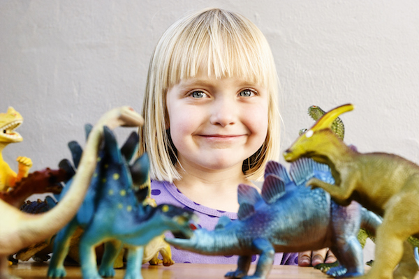 Little girl with toy dinosaurs