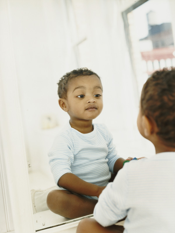 Young Boy Sitting in Front of a Mirror Looking at His Reflection